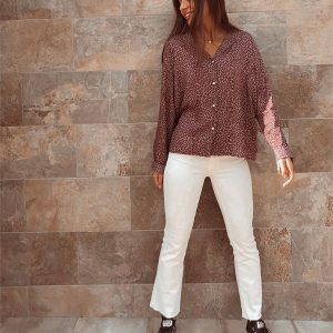 chica en frente de pared con pantalon cropped flare blanco